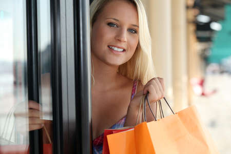 out door: Woman leaving a store with shopping bags