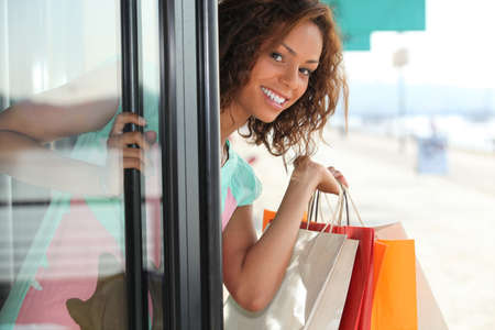 Woman with shopping bags coming out of shop photo