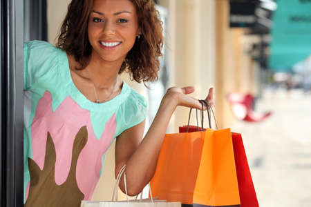 tienda de ropa: Mujer que salía de la tienda con bolsas de compras Foto de archivo