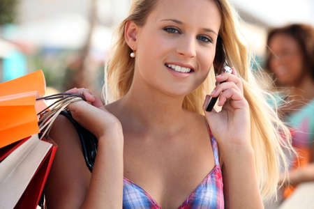Young woman talking on her mobile phone while shopping Stock Photo - 14012741