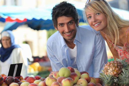 Young couple at a fruit stall in a market photo