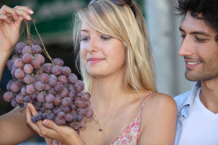 couple looking at huge bunch grapes photo