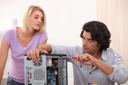 repair computer: man fixing computer with woman watching