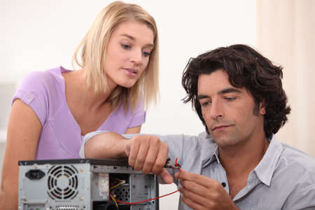 computer repairing: Man cutting a wire Stock Photo