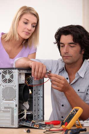 broken computer: Man repairing PC for colleague