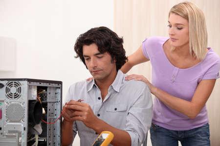 Technician repairing PC for attractive colleague photo