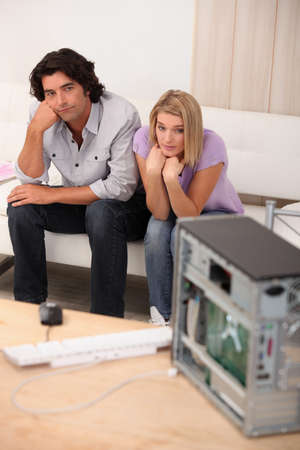 Couple sat in front of broken computer photo