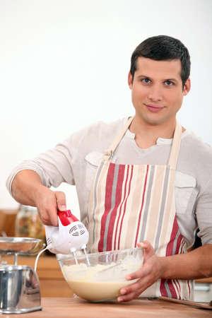 batidora: hombre joven con un batidor de huevos eléctrica