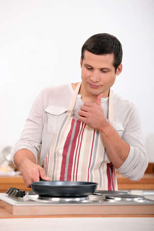 hobs: Young man in apron cooking