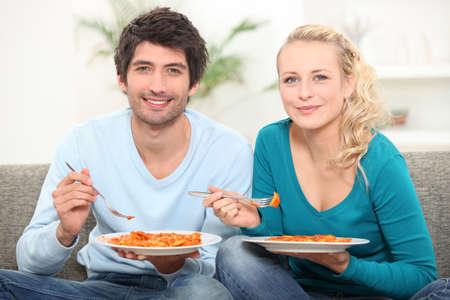 pareja comiendo: pareja cenando en el sofá