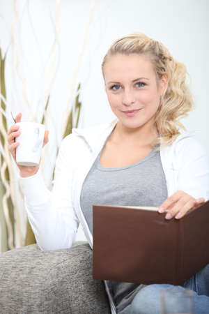 young woman sitting on sofa with photograph album and mug of coffee Stock Photo - 14012623