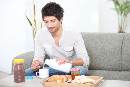 Young man having breakfast in his living room photo