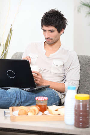 young having breakfast with computer on a sofa Stock Photo - 14014725