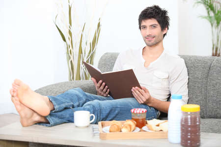 Man reading a book at breakfast Stock Photo - 14017988