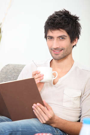 bookish: young man reading a book and drinking coffee on a couch Stock Photo