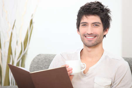 Man reading with coffee in hand photo