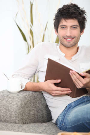 Man sat reading on sofa Stock Photo - 14027200