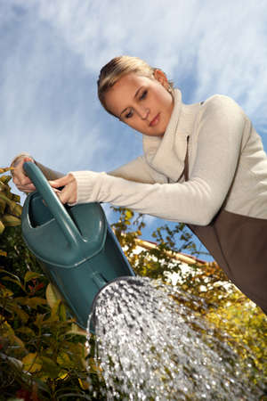 raising cans: Young woman with a watering can
