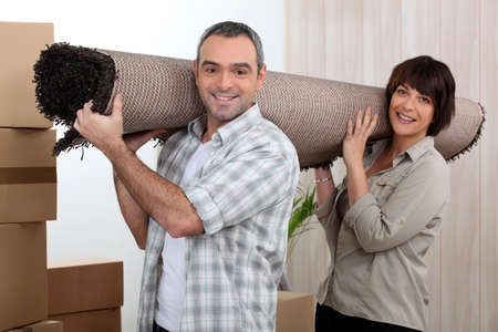 over shoulders: Couple carrying carpet over shoulders Stock Photo