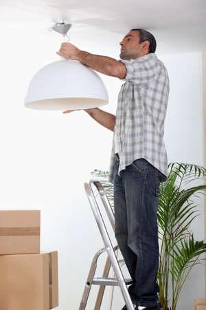 Man putting up a ceiling light photo