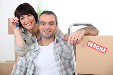 removals: Couple moving into new home with doorkeys and boxes marked fragile