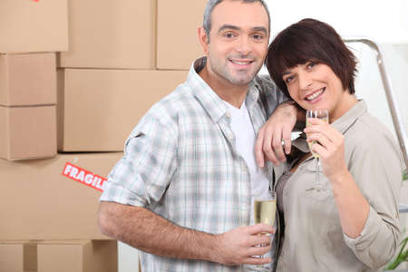 alcohol cardboard: Moving day for a couple celebrating with champagne Stock Photo