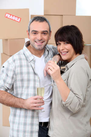 Couple drinking champagne in front of a pile of cardboard boxes photo