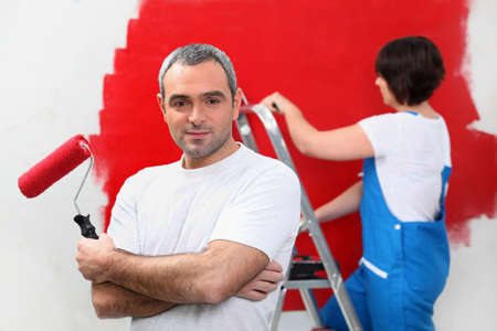 front raise: Couple painting wall red