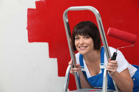 Brunette painting wall in red photo