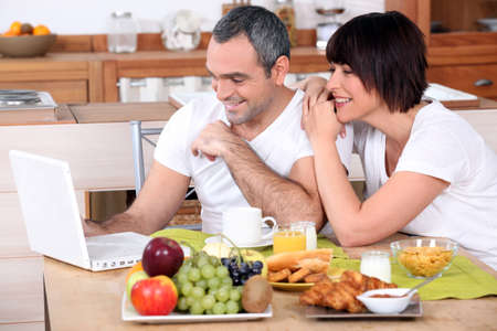 distraction: Couple looking at a laptop during breakfast