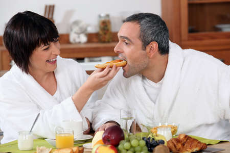Playful couple having breakfast photo