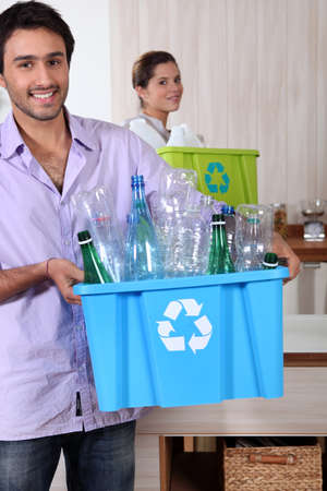 Couple recycling plastic bottles photo