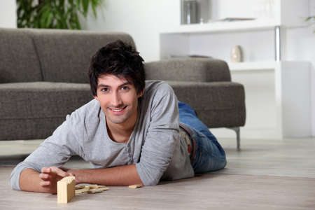 settee: Man playing with dominoes at home