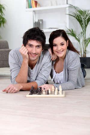 Couple playing chess lying photo