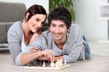 Couple laying on floor playing chess photo