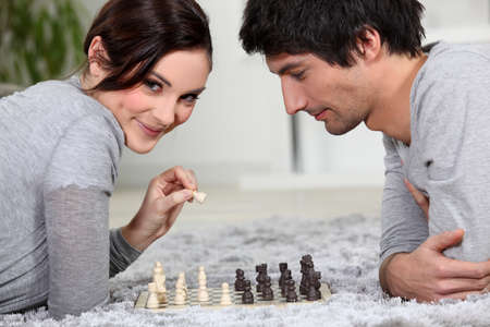 cute young couple playing chess together photo