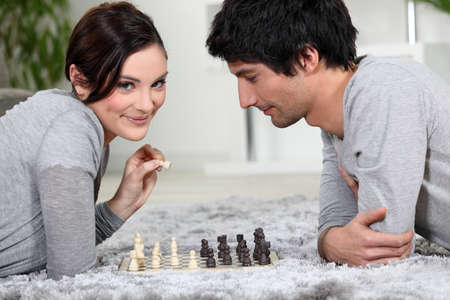 Couple playing chess whilst lying on the carpet Stock Photo - 14030071