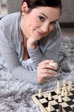 Young woman playing chess photo