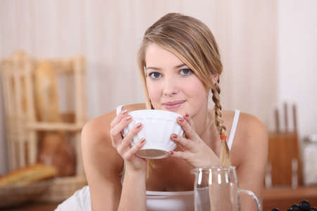 women face stare: Blond drinking from bowl at breakfast