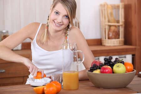 Woman making orange juice in kitchen photo
