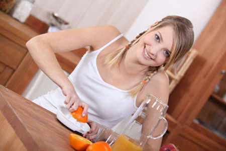 Girl squeezing orange juice photo