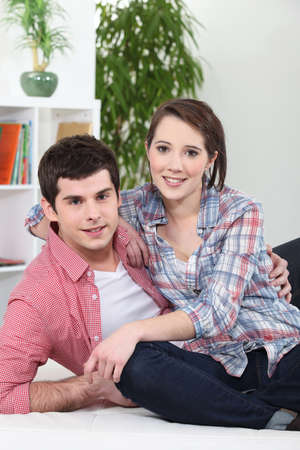 governed: Couple embracing on white sofa Stock Photo