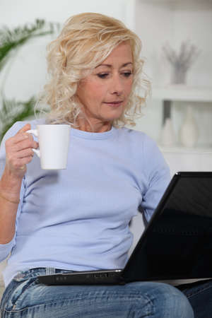 median age: Woman at computer with coffee cup