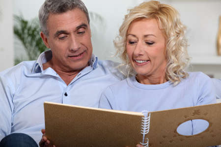Couple looking at a photo album Stock Photo - 13977543