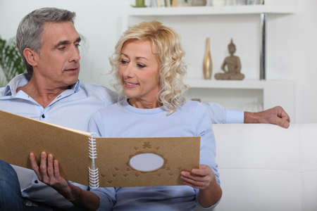 Mature couple looking at photo album photo