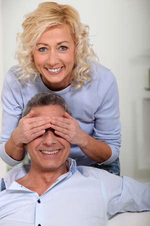 Woman covering her husbands eyes with her hands photo