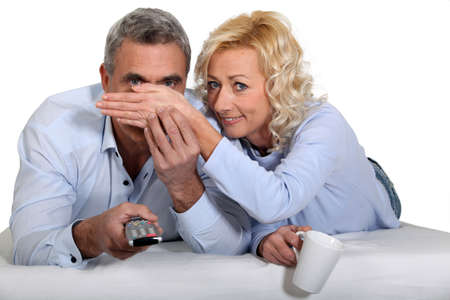 hand covering eye: Woman covering her husbands eyes during a scary film Stock Photo