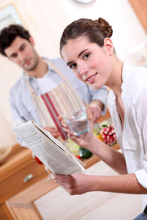 Couple in the kitchen with a newspaper photo