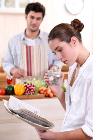 informed: Young woman reading a newspaper while her boyfriend prepares lunch