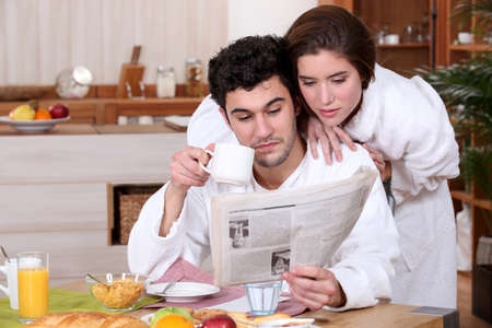 Young couple reading a newspaper at breakfast photo